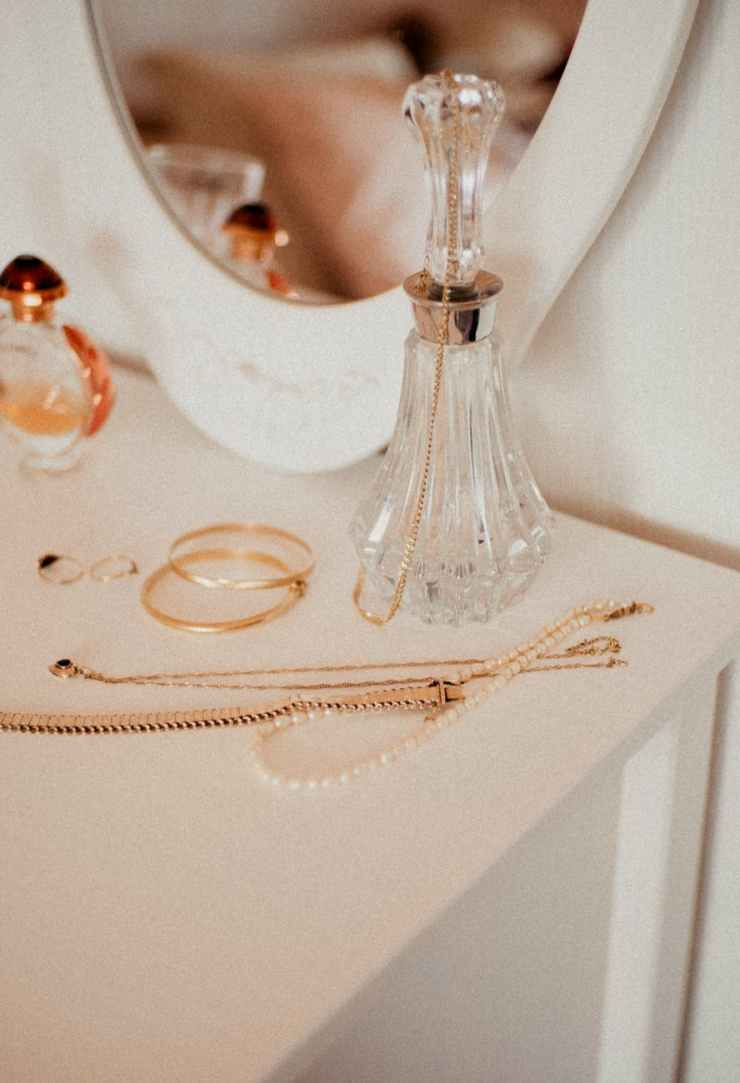 jewelries and clear glass bottle on white table