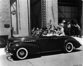 Bing Crosby giving rides around the studio lot in his 39 Olds coupe convertible