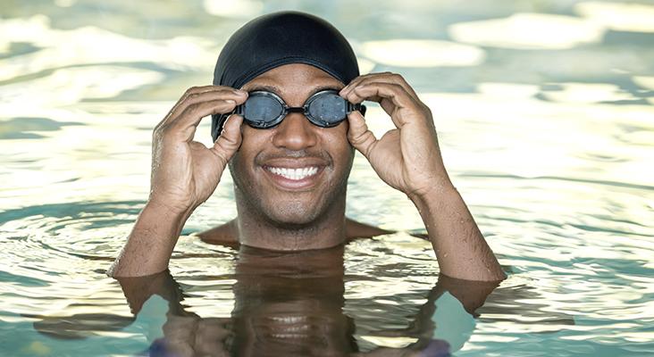man in pool wearing goggles