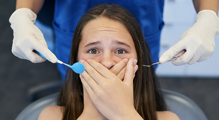 scared girl covering mouth in dentist chair