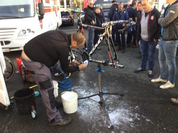 Mécanicien nettoyant le vélo après l'épreuve