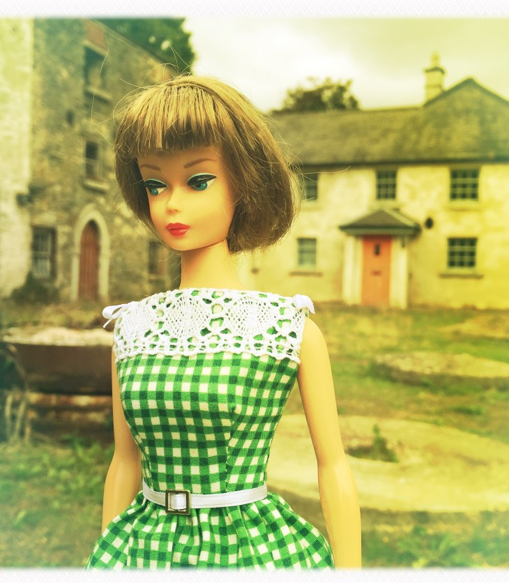 Vintage Barbie wearing a green check dress with vintage white lace trim
