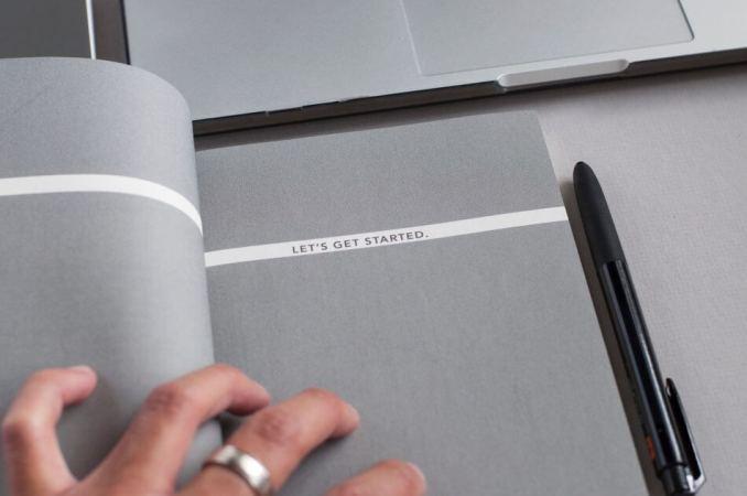 foto gambar tangan memegang buku yang di sebelahnya ada bolpoin pensil