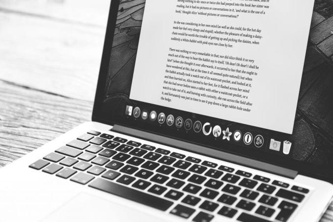 foto gambar laptop dengan banyak tulisan penulis lepas website blog