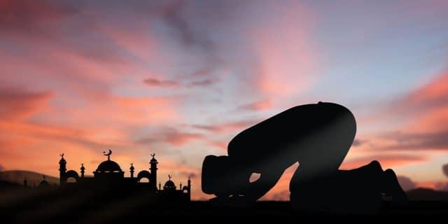 orang sedang melaksanakan sholat didepan masjid dan matahari terbit atau terbenam siluet