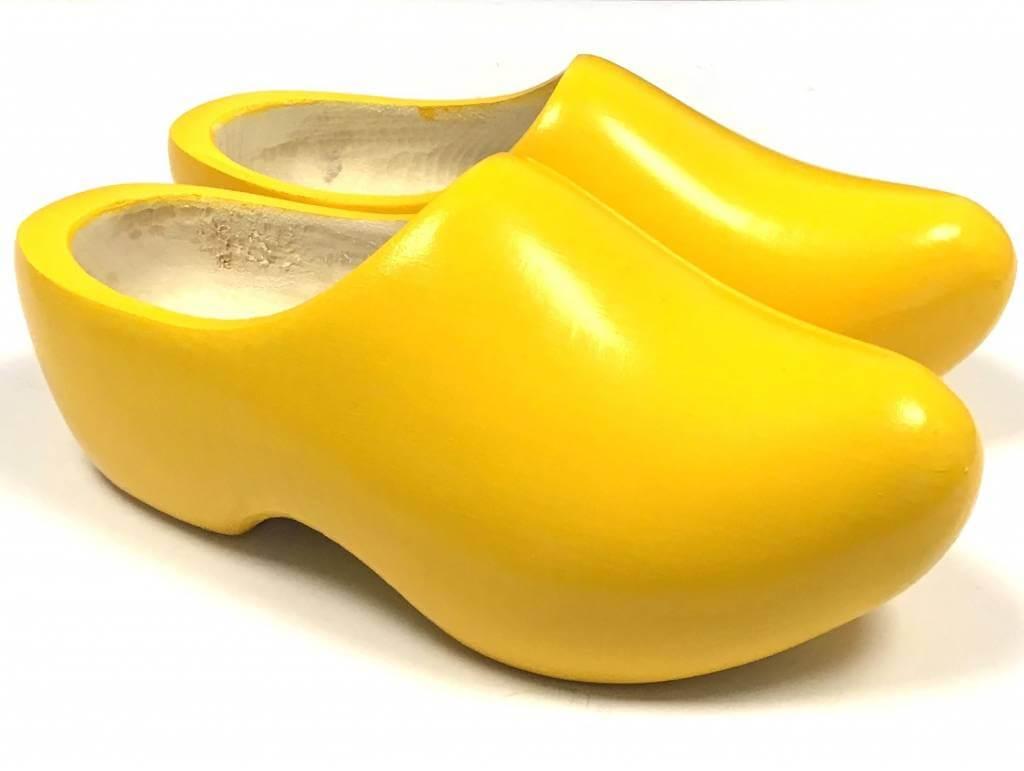 sepasang sepatu clogs warna kuning dengan latar belakang putih