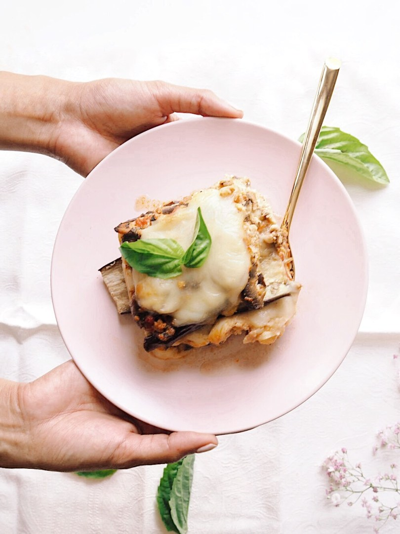Hands holding pink plate with slice of eggplant lasagna