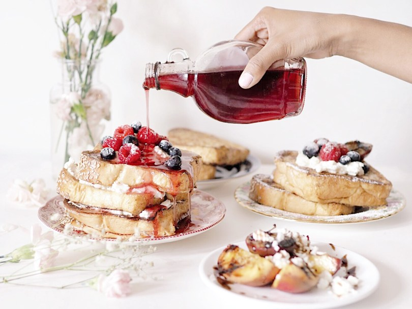 Pouring raspberry syrup on top of challah french toast