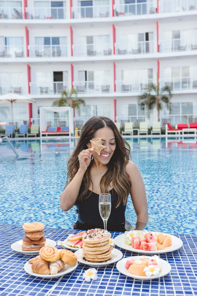 Holding starfish in front of breakfast spread at the pool