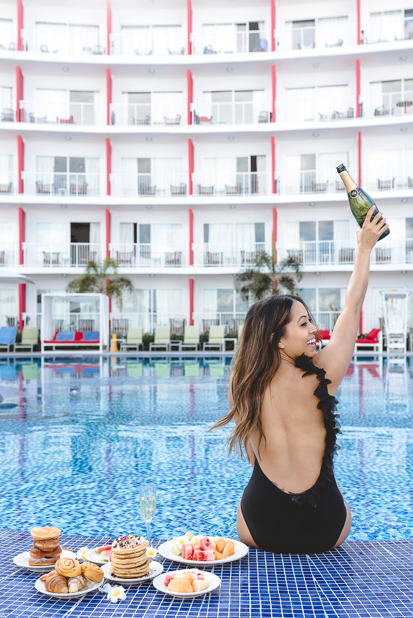 Holding up bottle of sparkling wine at the pool at Royal Decameron Cornwall Beach