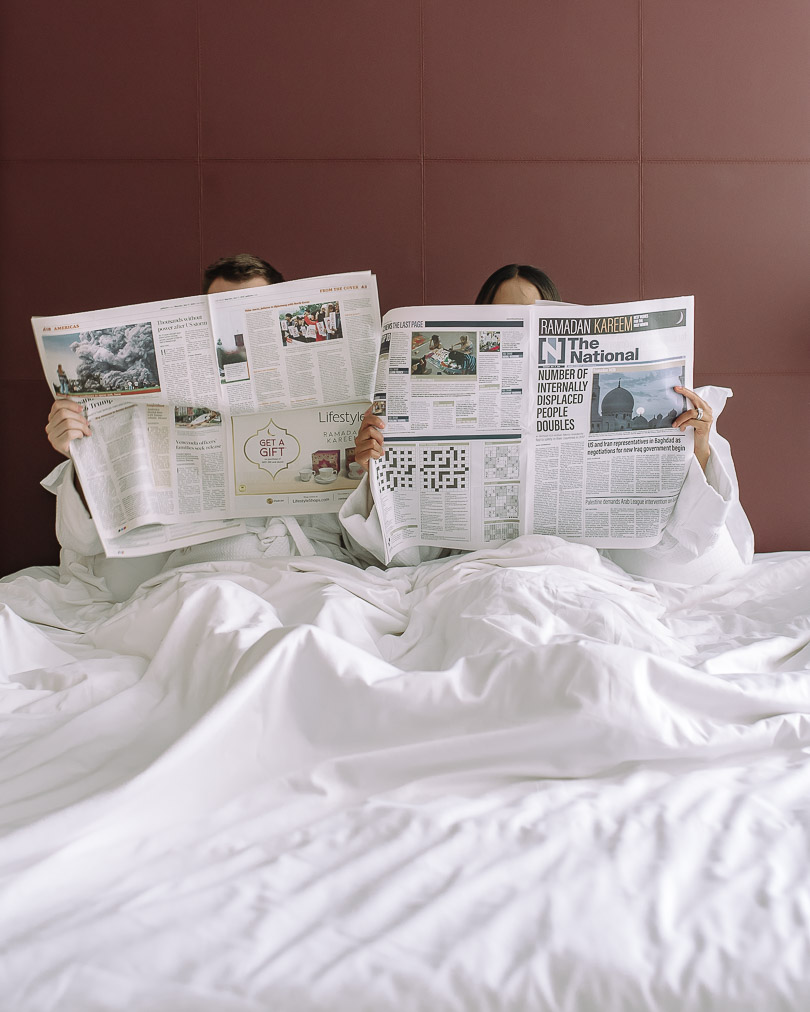 Sitting in hotel bed with newspaper