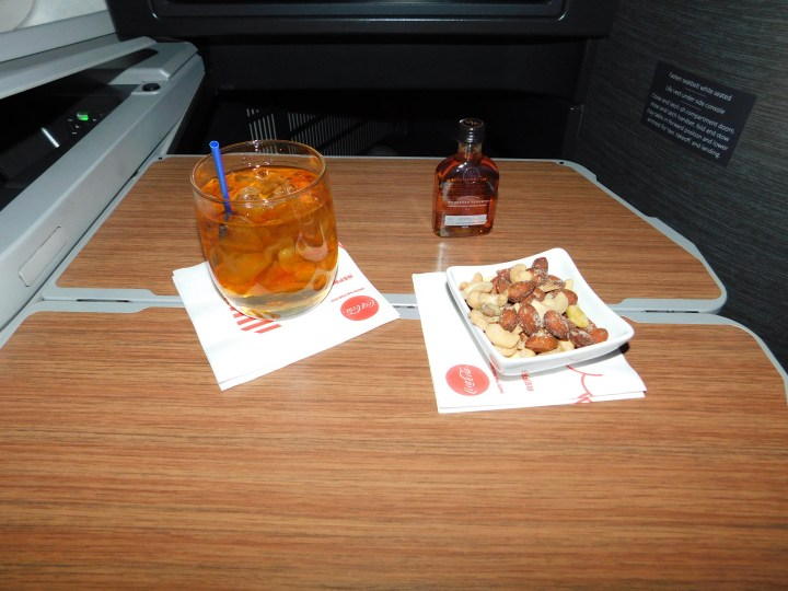 The American Airlines Hindu meal offers standard drink service. You are free to request whatever you see fit. I got the Woodford Reserve bourbon and warm mixed nuts.