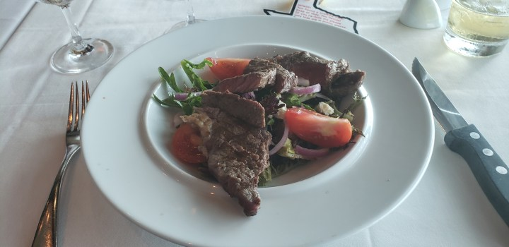 The NY steak salad at Chops Grille on the Liberty of the Seas in July 2019. Royal Caribbean specialty menus cost extra, but they provide an alternative to the MDR and the buffet.