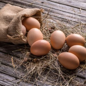 Fresh brown eggs on rustic background