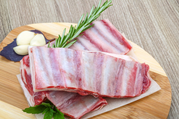 Fresh cold Raw lamb ribs with garlik and pepper - ready for cooking