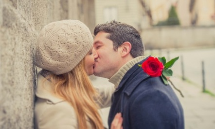 Picture of couple kissing with rose.