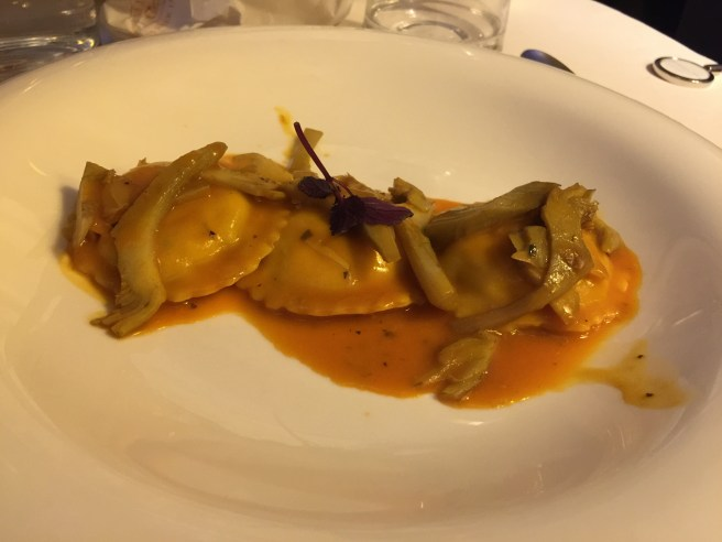 Homemade ravioli of sea bass with shellfish bisque and artichokes