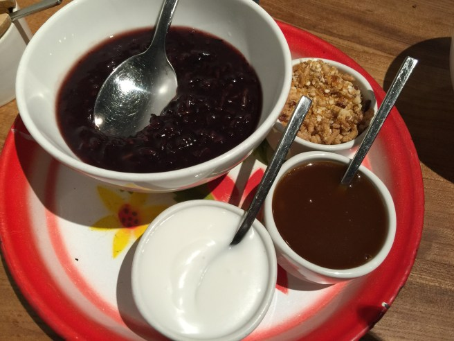 Black sticky rice dessert with crumbles, caramel and cream