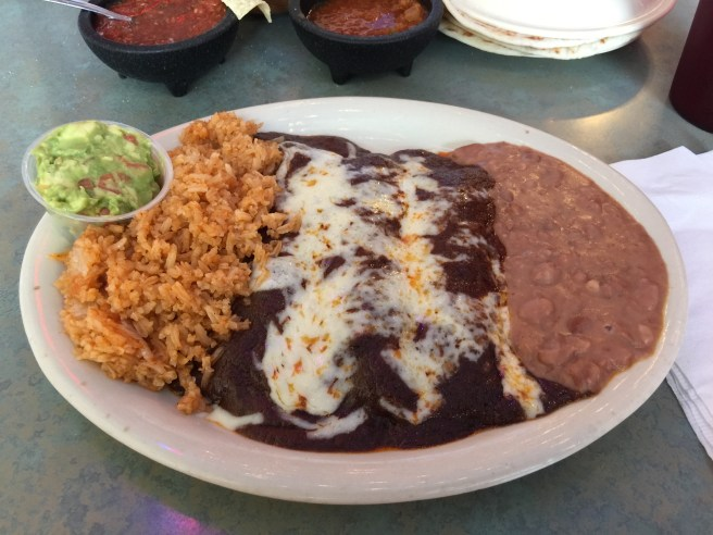 Chicken Molé Enchiladas with beans and rice and a side small guacamole