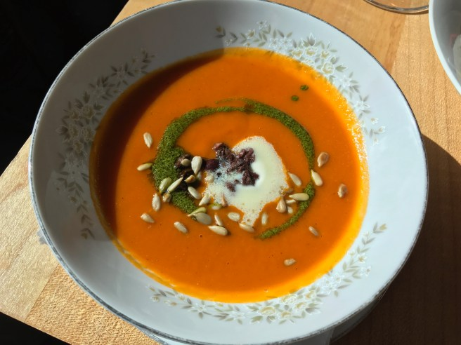 Tomato soup with savory salsa verde, spiced sunflower seeds, creme fraiche and Nicoise olives