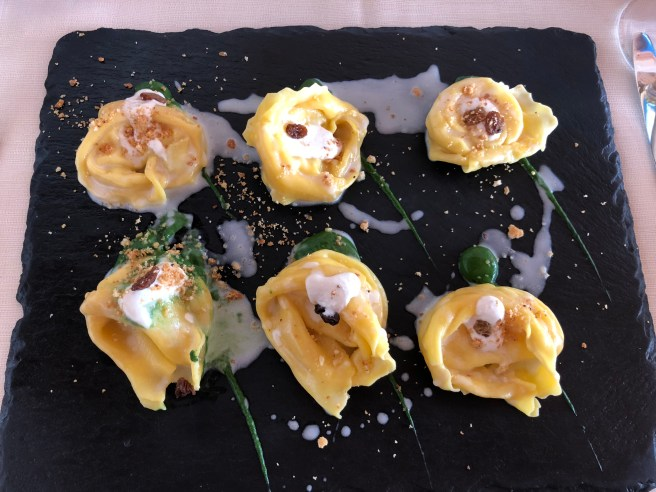 Home made cappellacci pasta filled with fossa's pecorino cheese and potatoes on cream of spinach, raisins and pine nuts