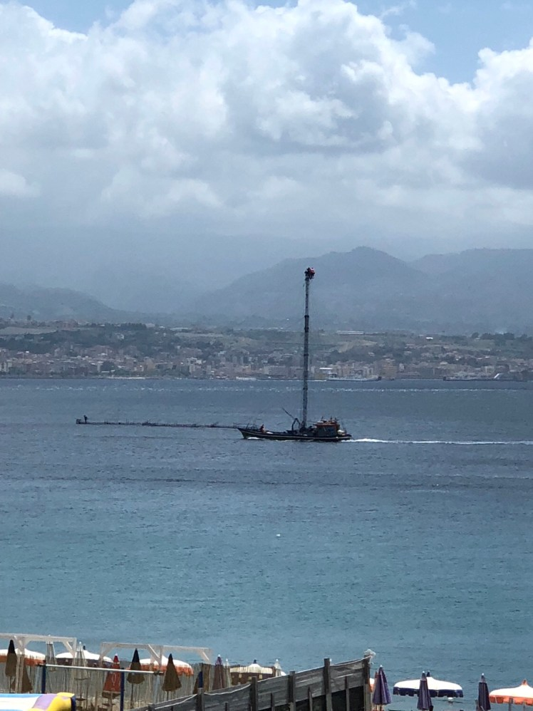 A traditional, Sicilian feluca ship searching swordfish in the Messina Strait