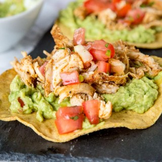 chicken tostada with guacamole on a plate