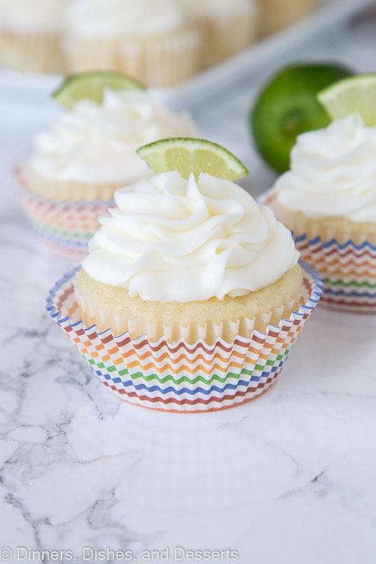 close up of margarita cupcakes topped with frosting and a lime slice