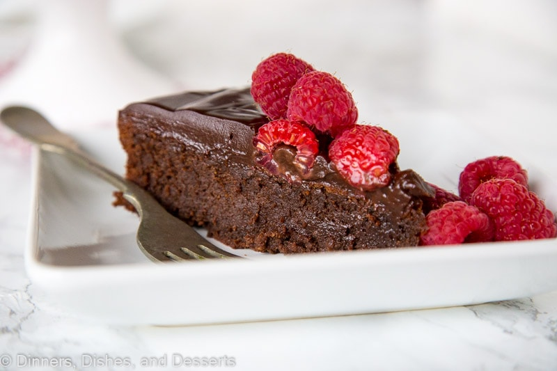 Flourless Nutella Cake - A rich and fudgy flourless chocolate cake full of Nutella! Top with raspberries for hazelnuts for a decadent dessert.