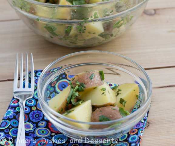 Lemon-Herb Potato Salad in glass bowl on wood board with fork