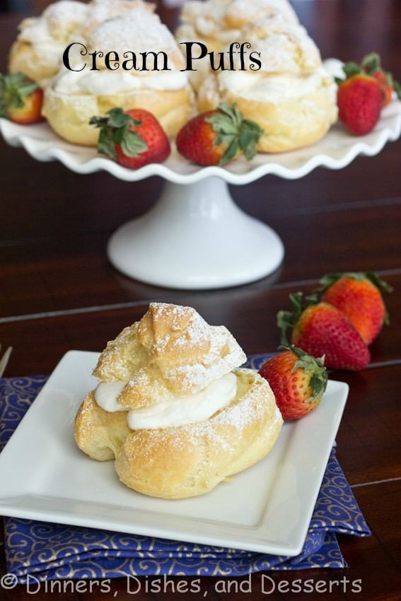 A plate of cream puffs on a table, with Cream and Pastry
