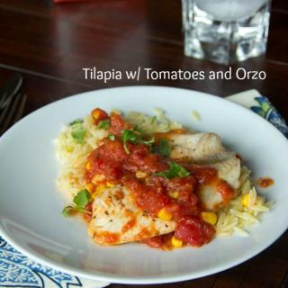 tilapia with tomatoes and orzo on a plate