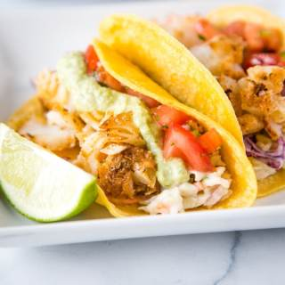 A plate of fish tacos with different toppings, with Taco