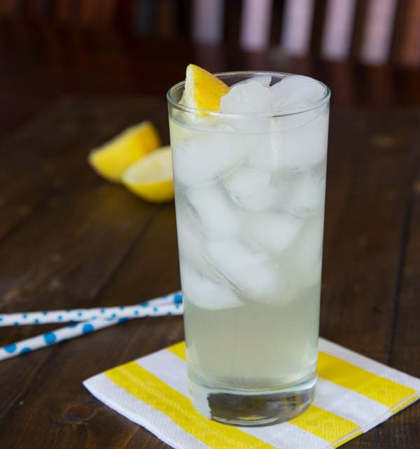 A cup of lemonade sitting on top of a wooden table, with Lemon and Lemonade