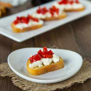 Piquillo Pepper and Goat Cheese Crostini - crispy crostini topped with goat cheese, chopped piquillo peppers and drizzled with balsamic vinegar. The perfect easy appetizer for any get together.