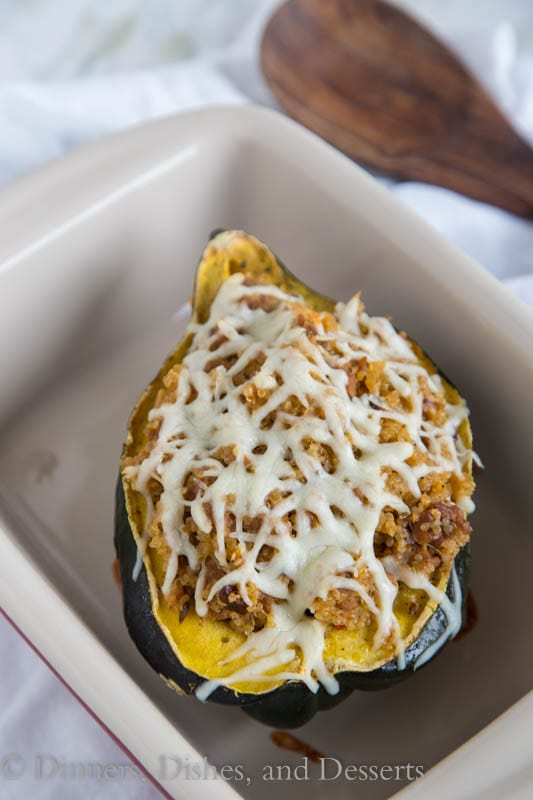 Quinoa and Sausage Stuffed Acorn Squash - Sweet acorn squash stuffed with spicy Italian sausage, quinoa, sweet dried cranberries and walnuts. A perfect fall dinner that can be even be made ahead of time!