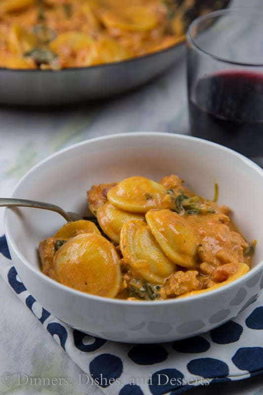 Creamy Sausage and Tomato Ravioli Recipe - A creamy one pot pasta with Italian sausage, tomatoes, and fresh spinach, done in 20 minutes! Even your pickiest eater will love it! Add to our dinner rotation now!