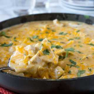 a skillet with chicken and cheese