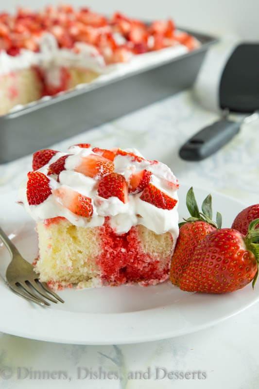 Poke cake with strawberry jello and fresh shipped cream in white pate