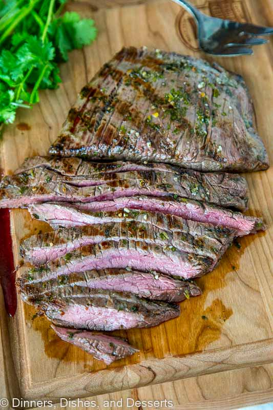 A sliced steak sitting on top of a wooden cutting board, with Steak and Taco