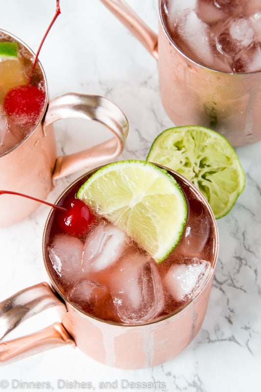 A close up of Cherry Lime and Moscow mule in a glass with lime slices