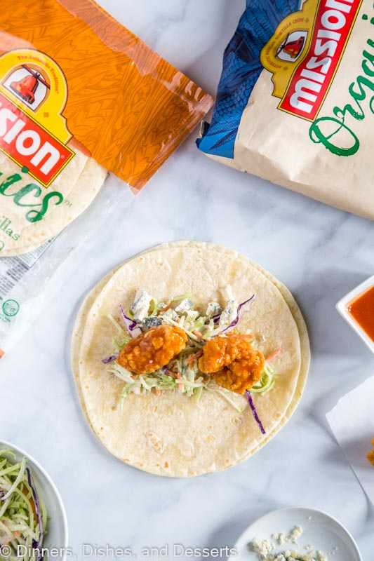 Crispy Buffalo Chicken Wrap - crispy chicken strips tossed with buffalo sauce and wrapped up with a creamy ranch coleslaw and blue cheese crumbles. A great lunch or easy dinner for the whole family!