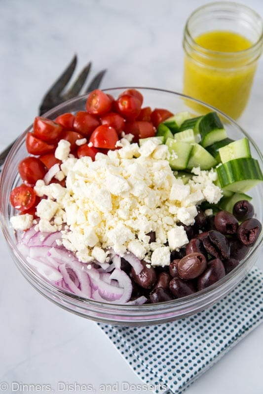Greek salad recipe with dressing in bowl ready to be mixed together