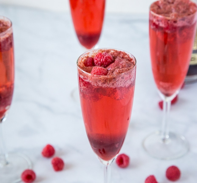 Raspberry Mimosas - A great drink for brunch or your next party.  Raspberry sorbet, champagne, raspberry liqueur and a few fresh raspberries make for a delicious cocktail.