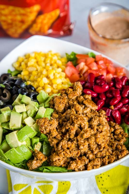 Taco salad with beans, tomatoes, corn, avocado, black olives, taco meat, and cheese Doritos