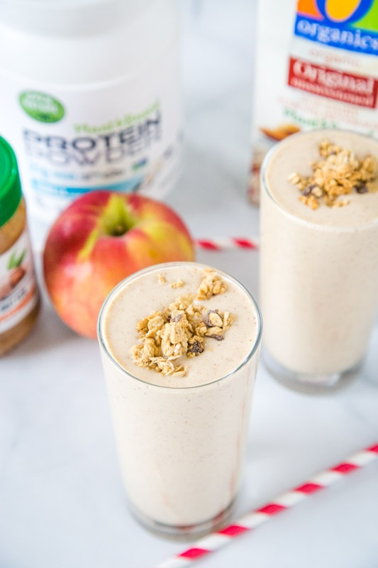 apple smoothie in a glass with milk, apple, protein powder and almond butter in background