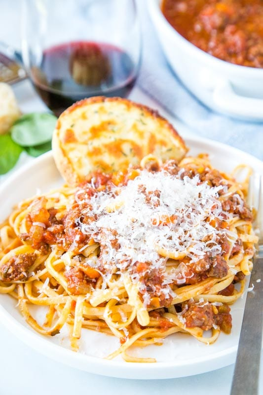 Plate of pasta with meat sauce topped with parmesan cheese