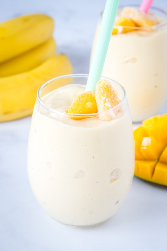 mango smoothie in a glass with sliced mango next to it