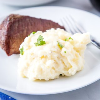 cropped mashed potatoes on a white plate with steak