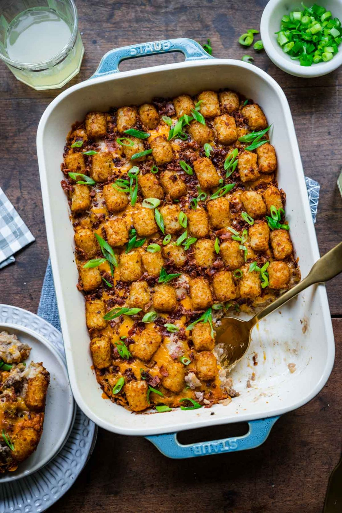 Finished Bacon Cheeseburger Tater Tot Casserole in 9x13 pan with bacon and green onions garnish